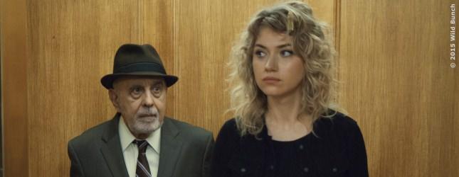 Izzy (Imogen Poots) im Hotelaufzug auf dem Weg zu ihrem Date mit Arnold, beschattet von Detektiv Fleet (George Morfogen)